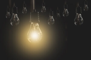 Hanging light bulbs with glowing one on dark background. Concept - light bulb moment when ERP business requirements are clear
